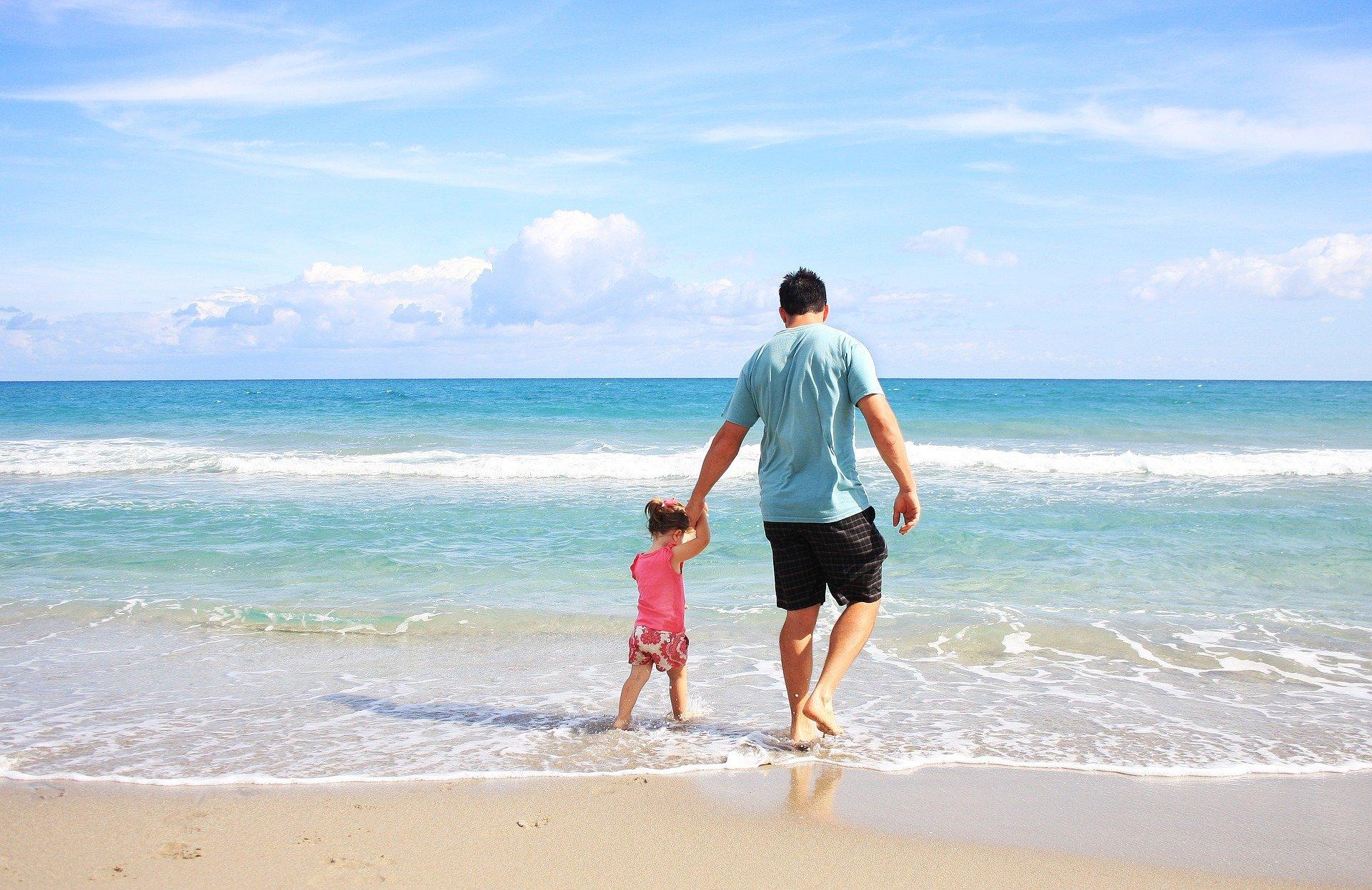 Tată cu fetița pe plajă