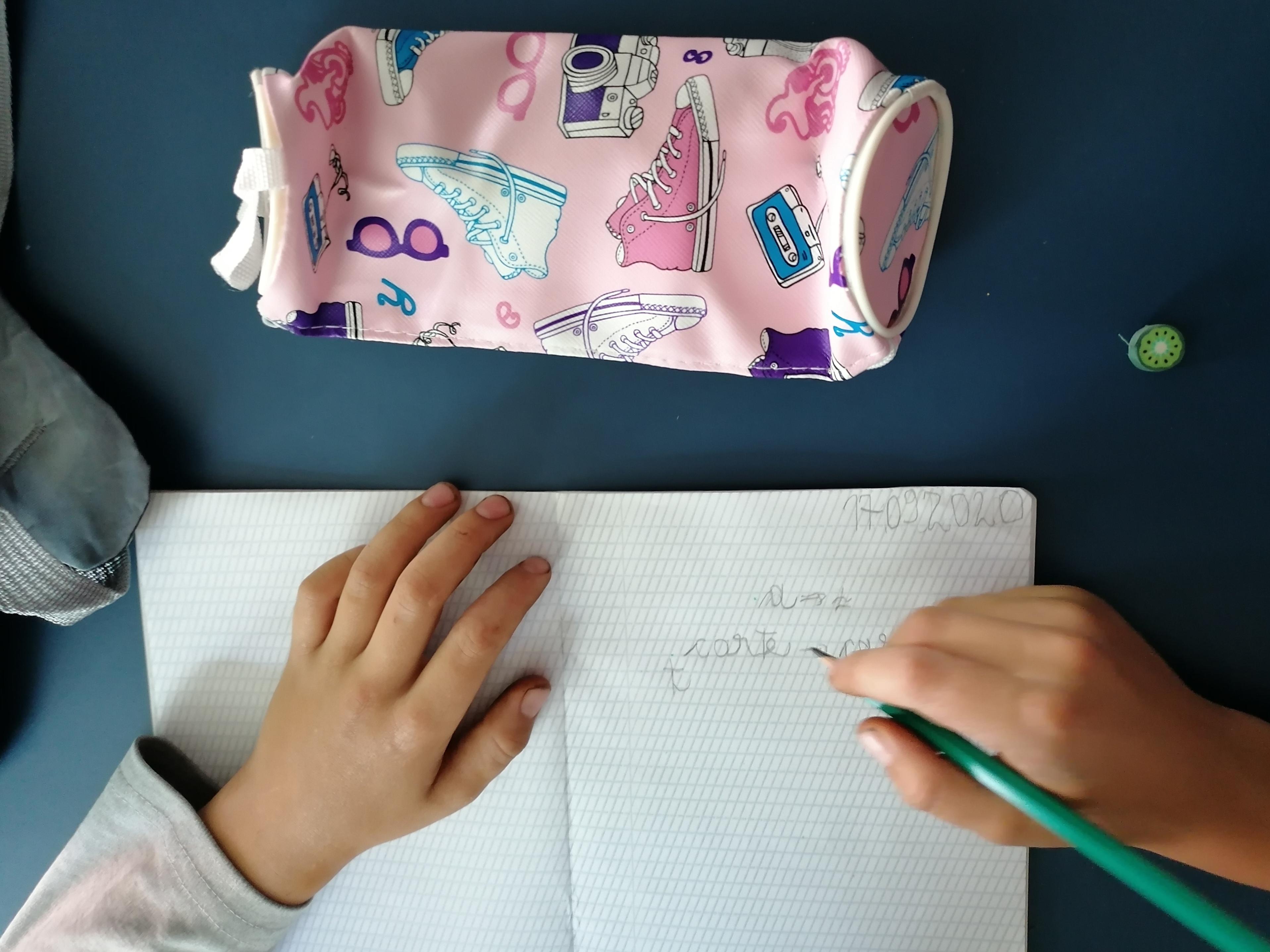 copil care scrie pe caiet