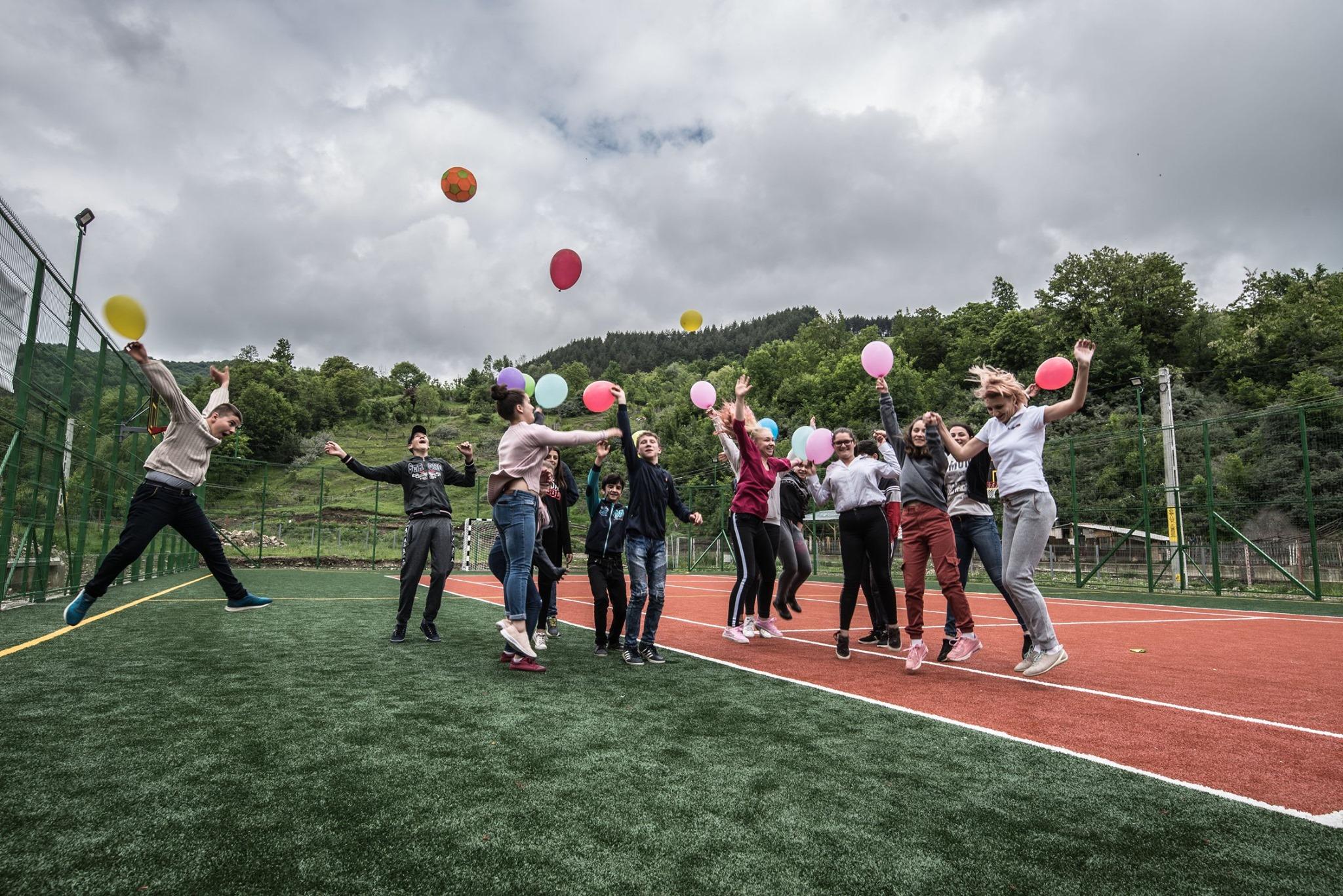 Alina Mirt înconjurată de copii, pe un teren de sport nou construit