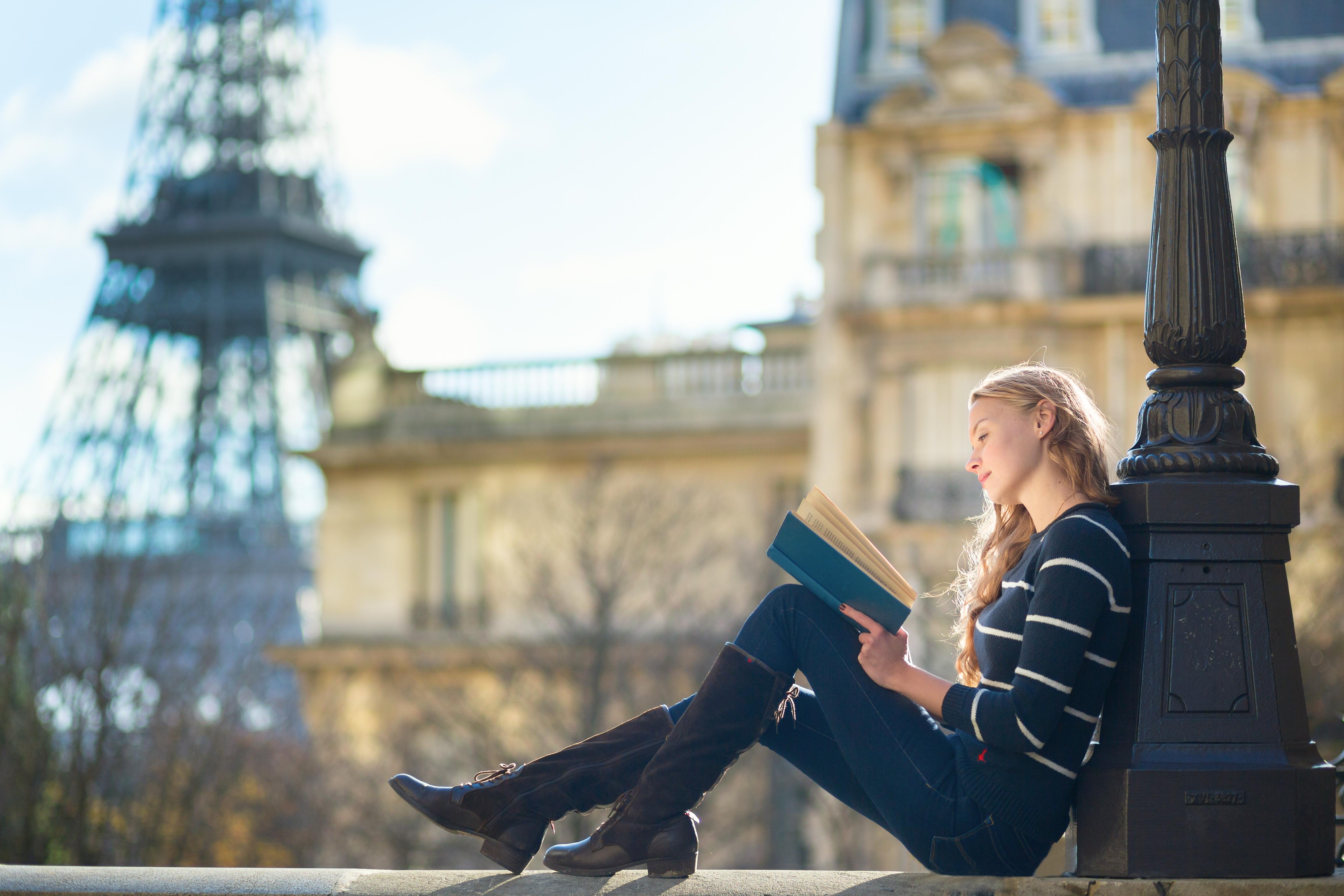 Tanara care citeste avand in planul doi Turnul Eiffel
