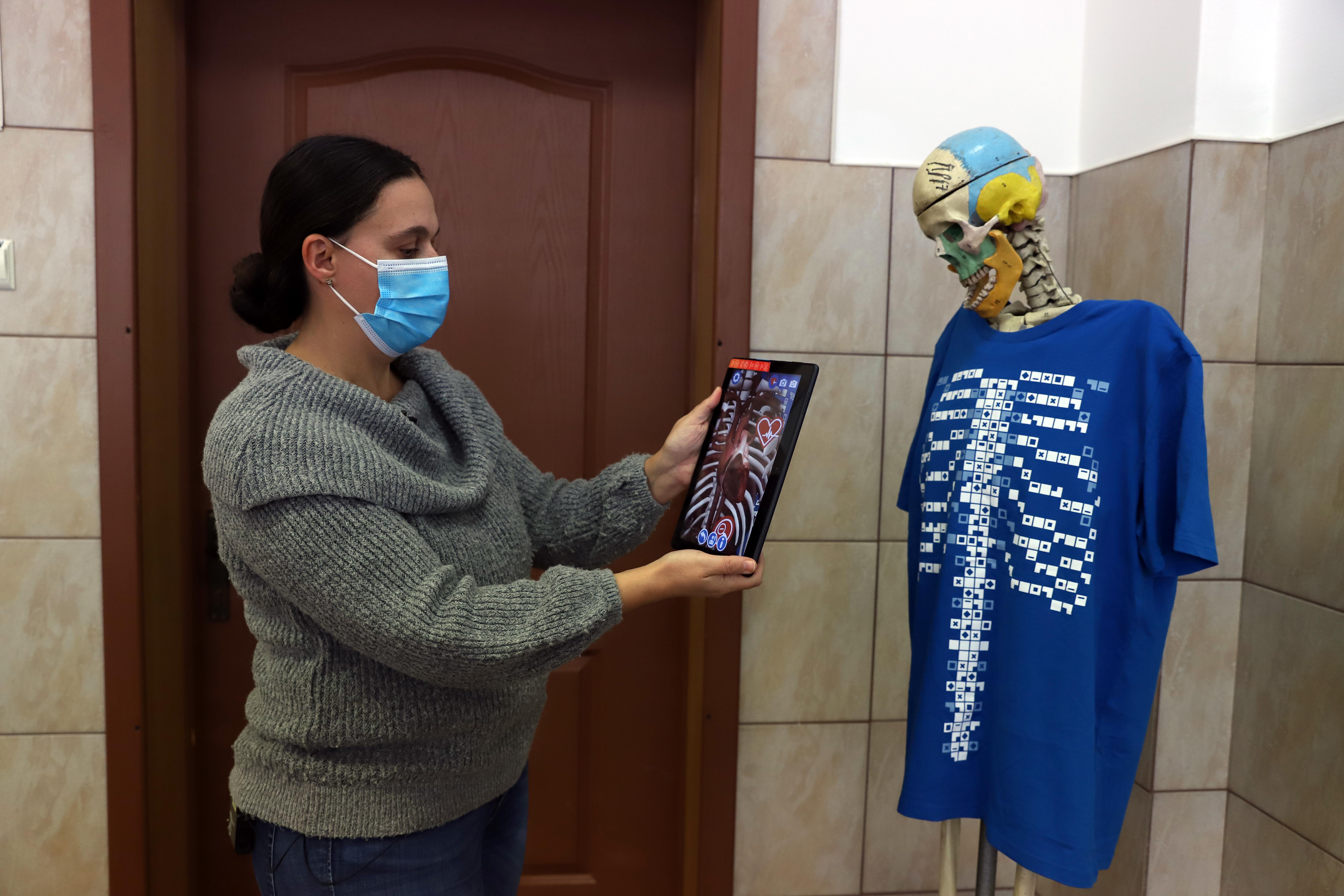 Profesoara de fizică lângă scheletul Gică, îmbrăcat în tricoul de realitate augmentată