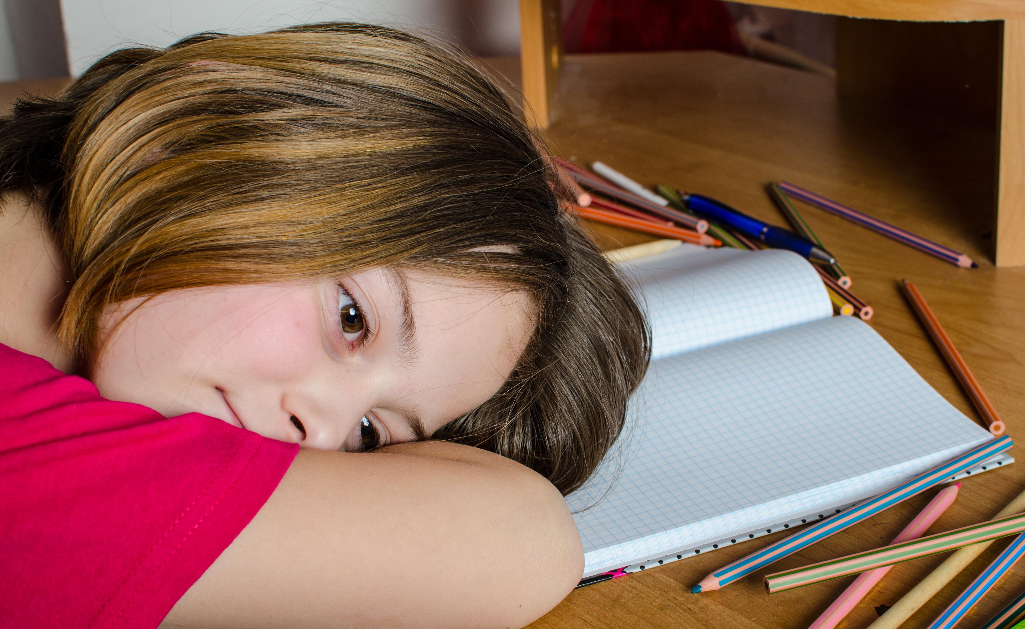 copil care sta cu capul pe caiet
