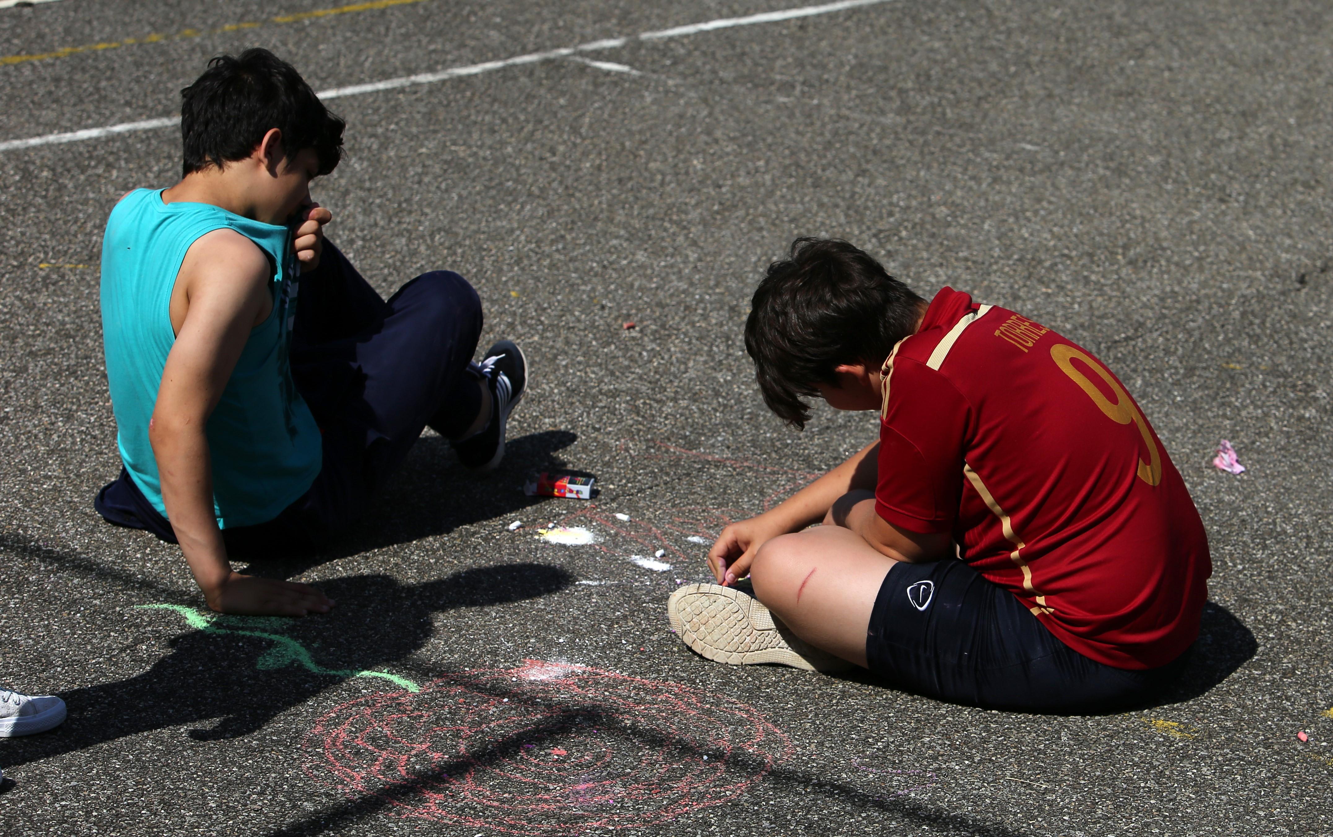 Copii desenând cu cretă