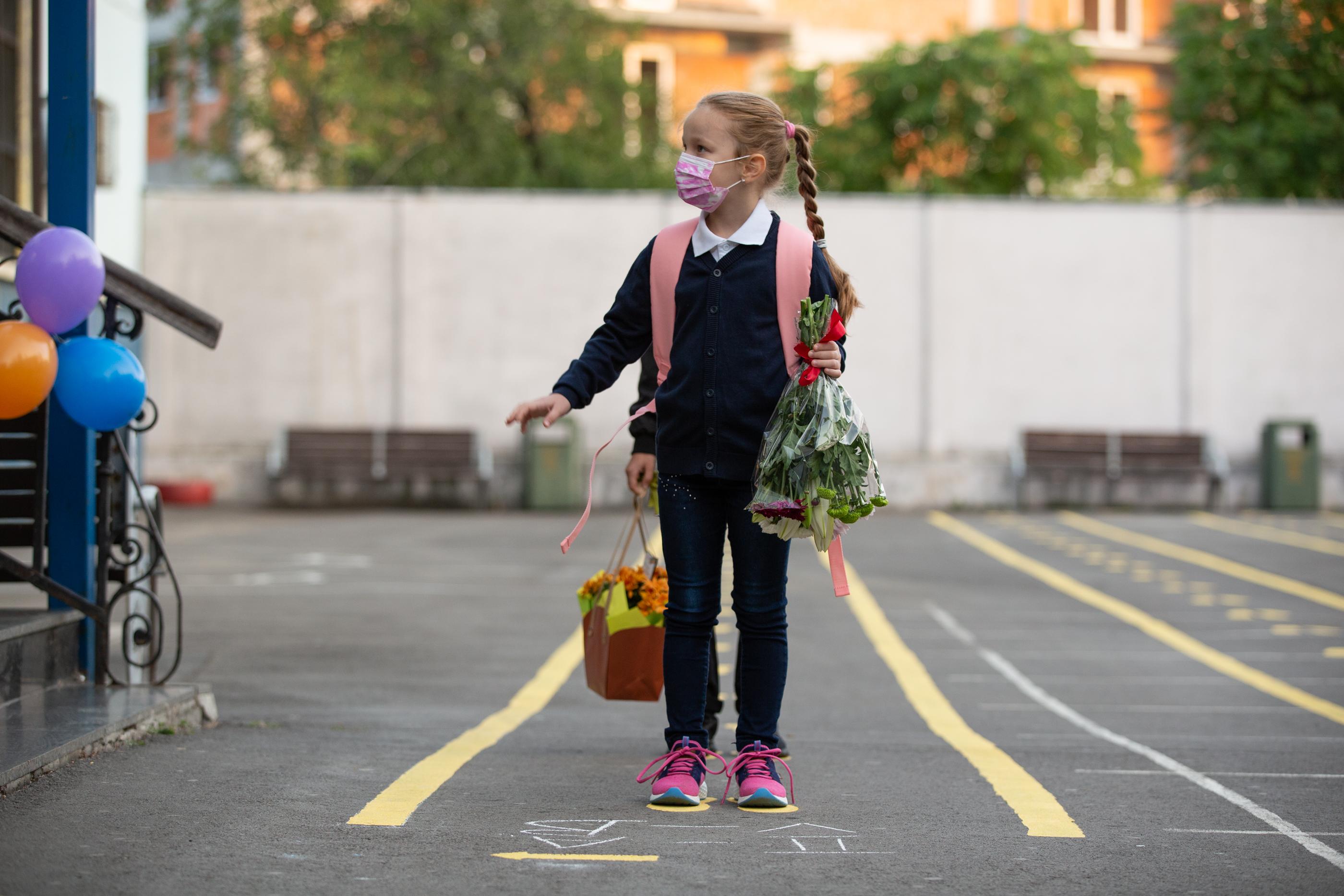 O fetită în uniformă în curtea școlii