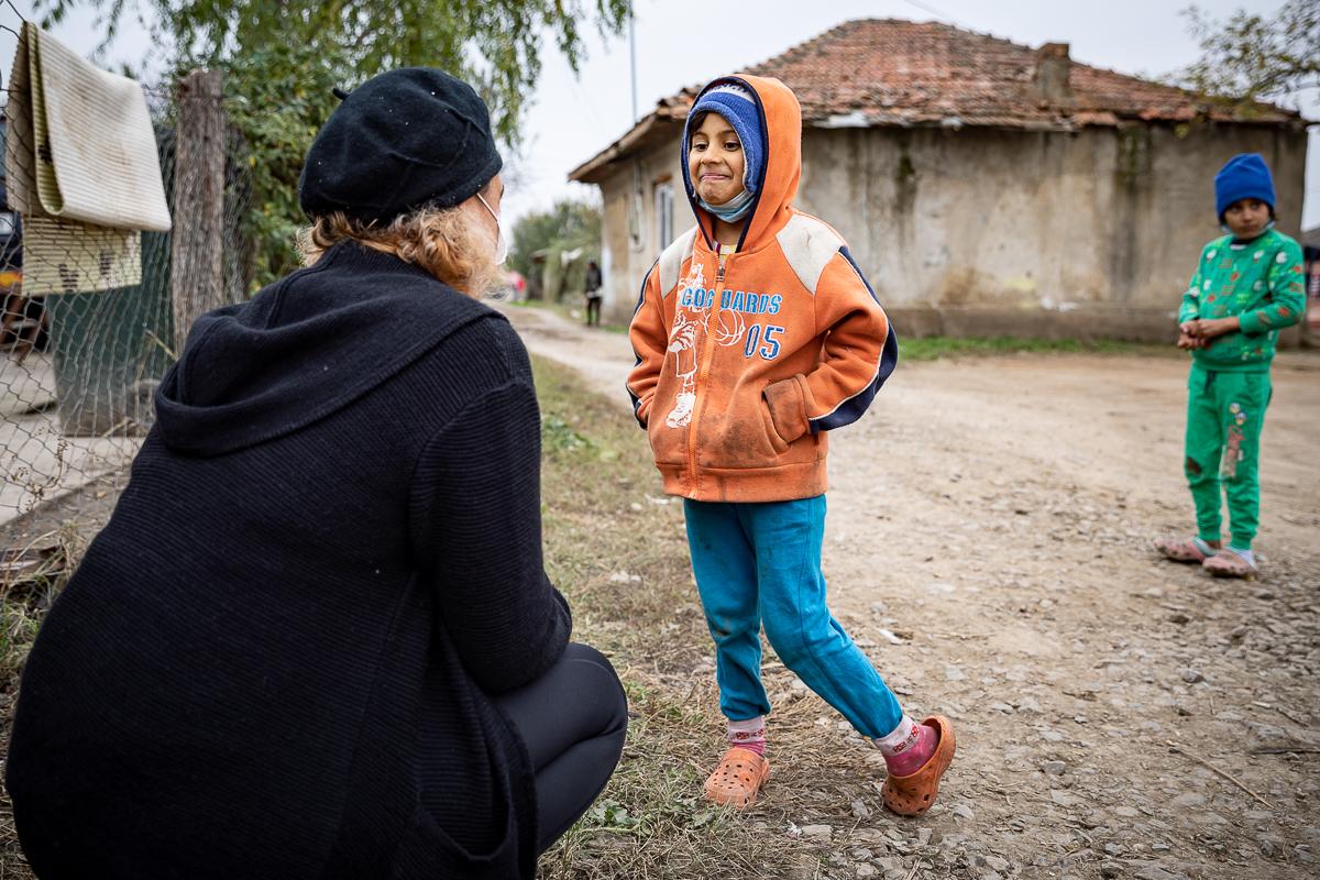 O învățătoare vorbește în stradă cu un copil
