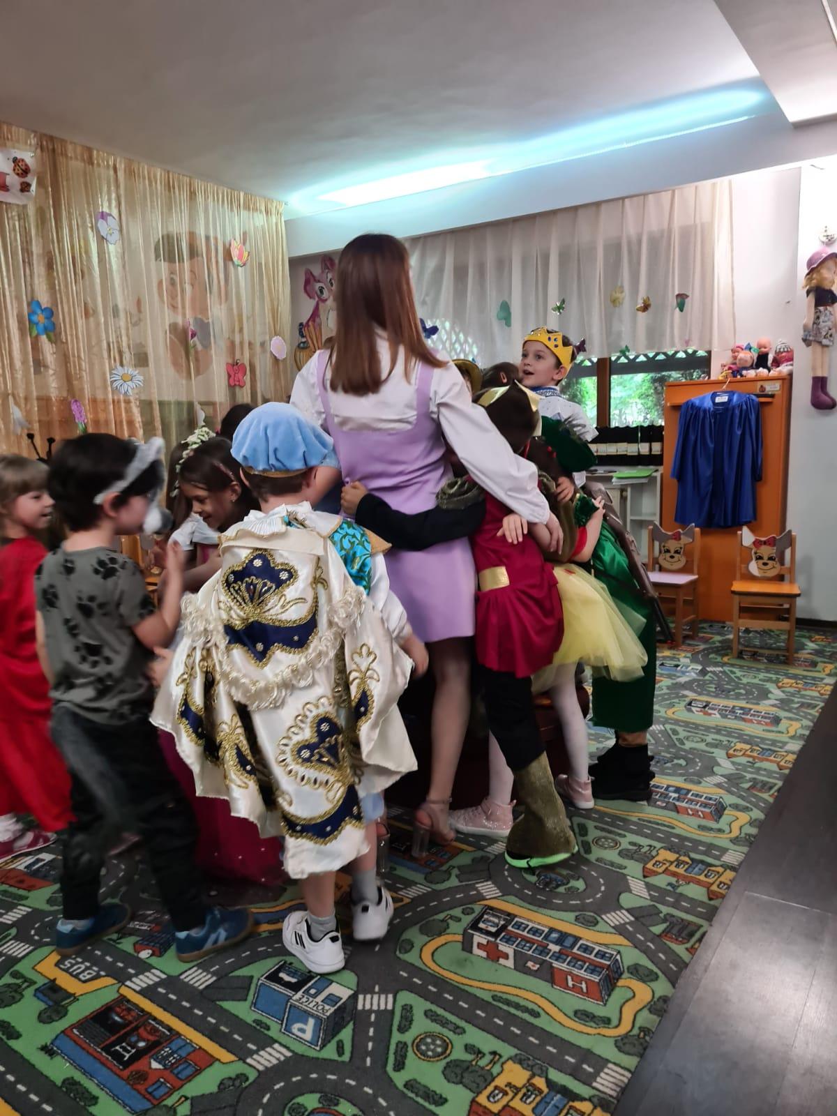 copii strângându-și în brațe educatoarea