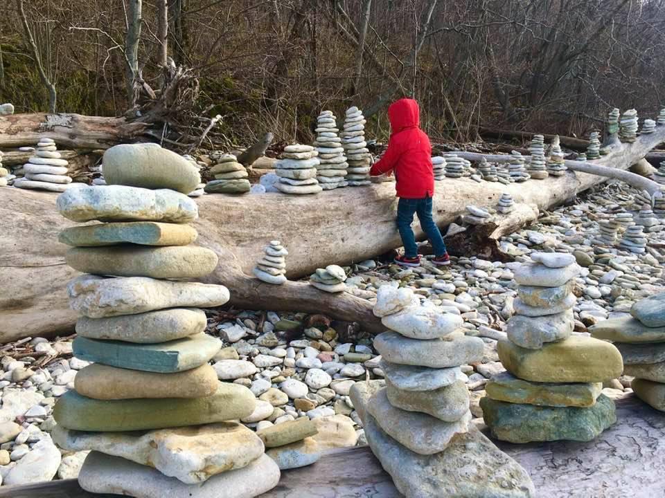Copil făcând castele din pietre