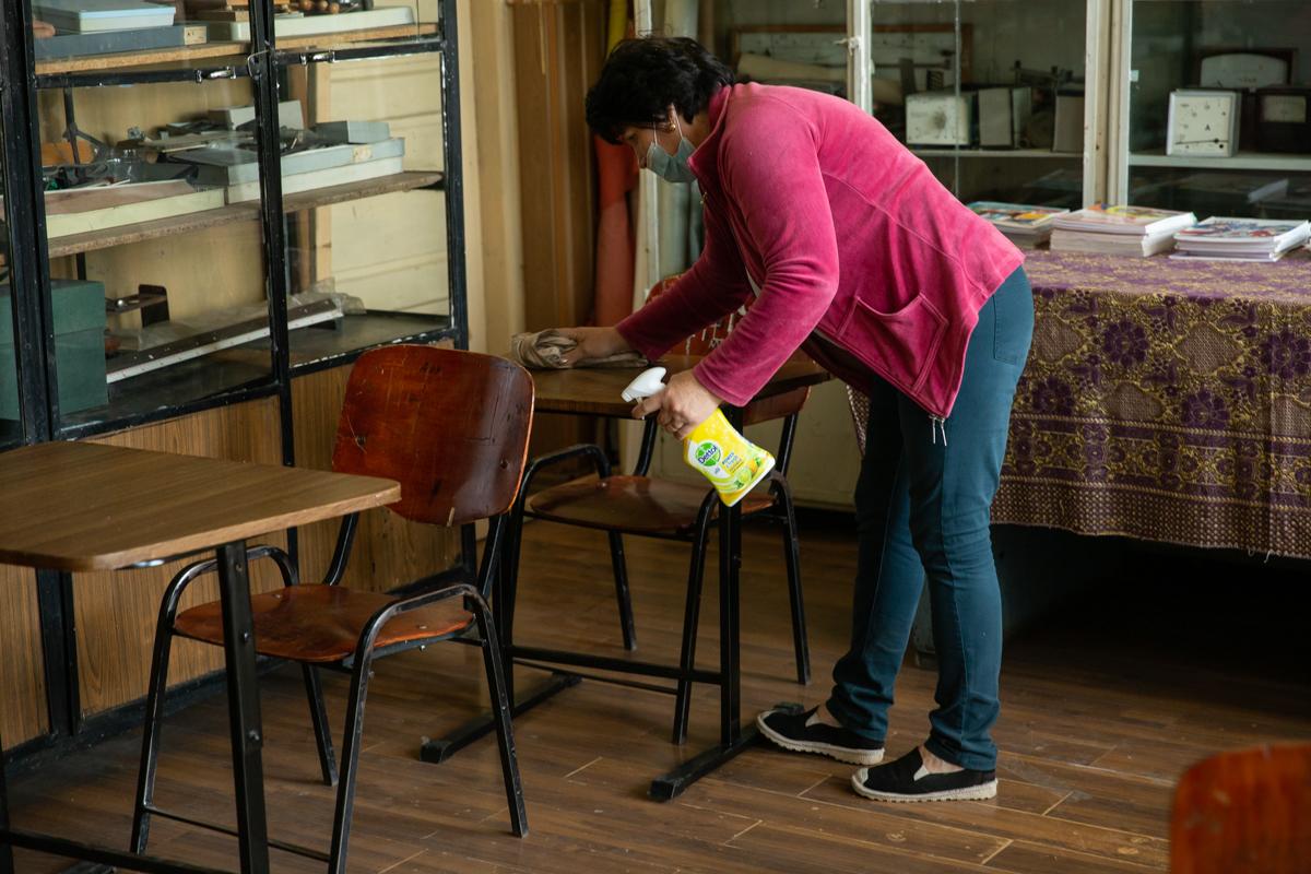 O femeie de serviciu face curățenie în clasă