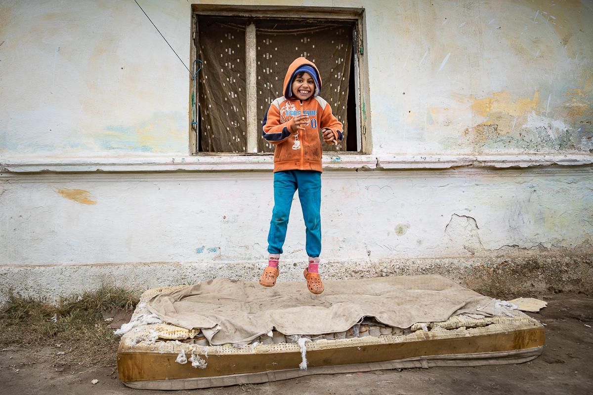 Un copil sare pe o saltea murdară în curte