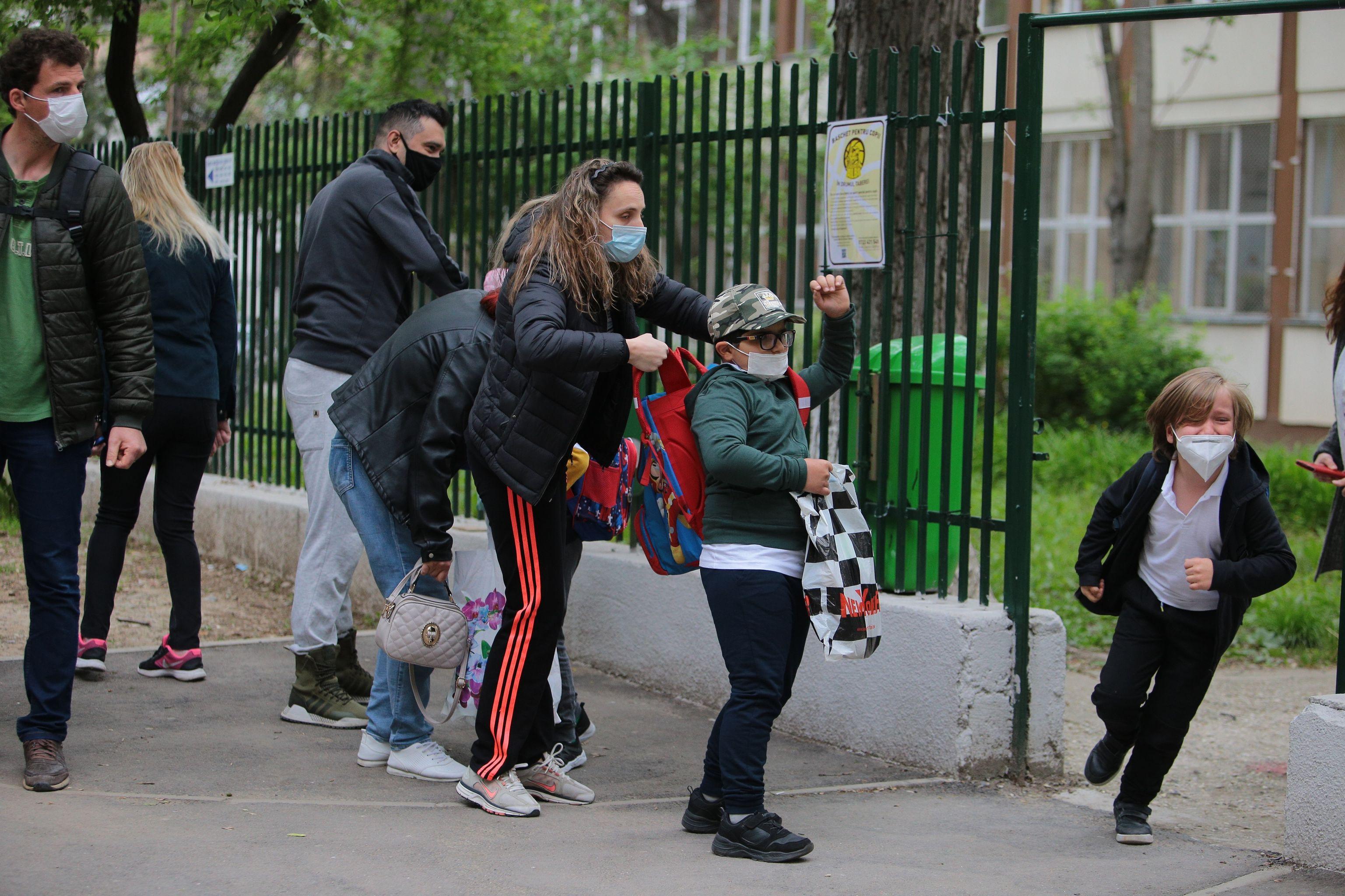 Copil fugind pe poarta școlii