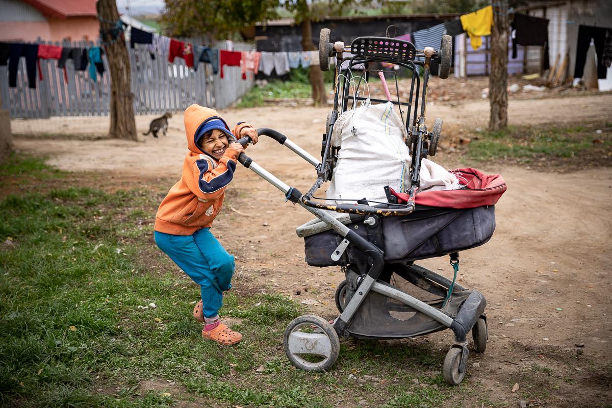 Copil care se joacă cu un cărucior plin de vechituri