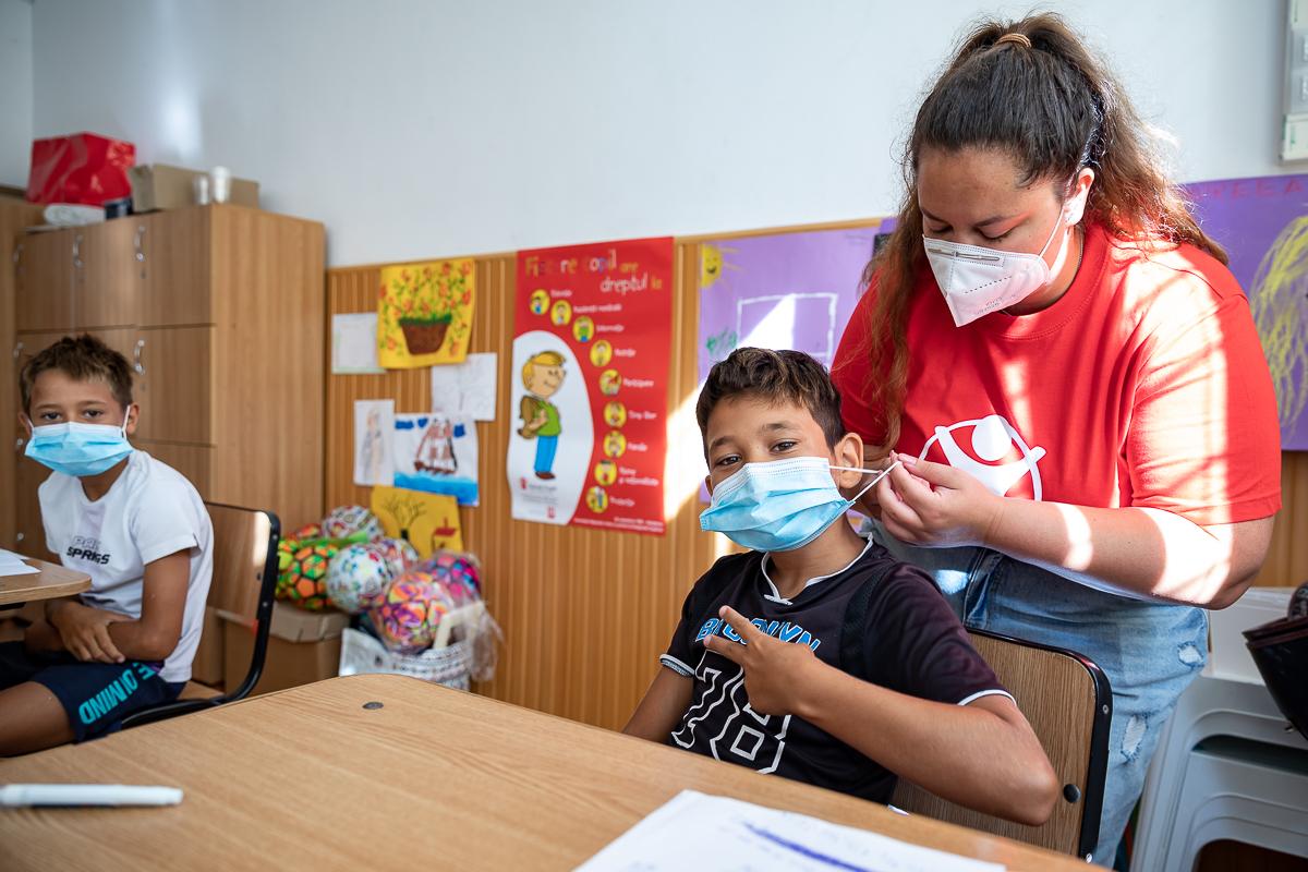 Maria Fățoi, unul dintre voluntarii Salvați Copiii, îi aranjază masca lui Ricardo Său. În stânga, este fratele său Antonio.