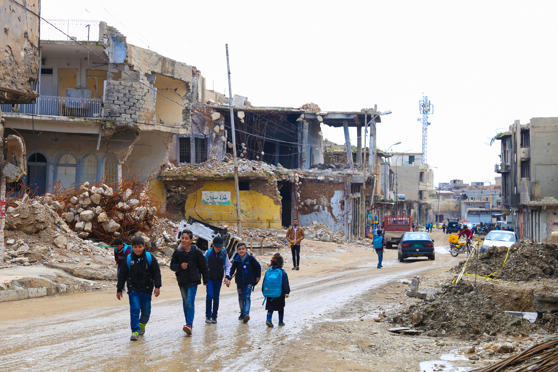 Mosul, Irak. Copii care merg la școală printre ruine