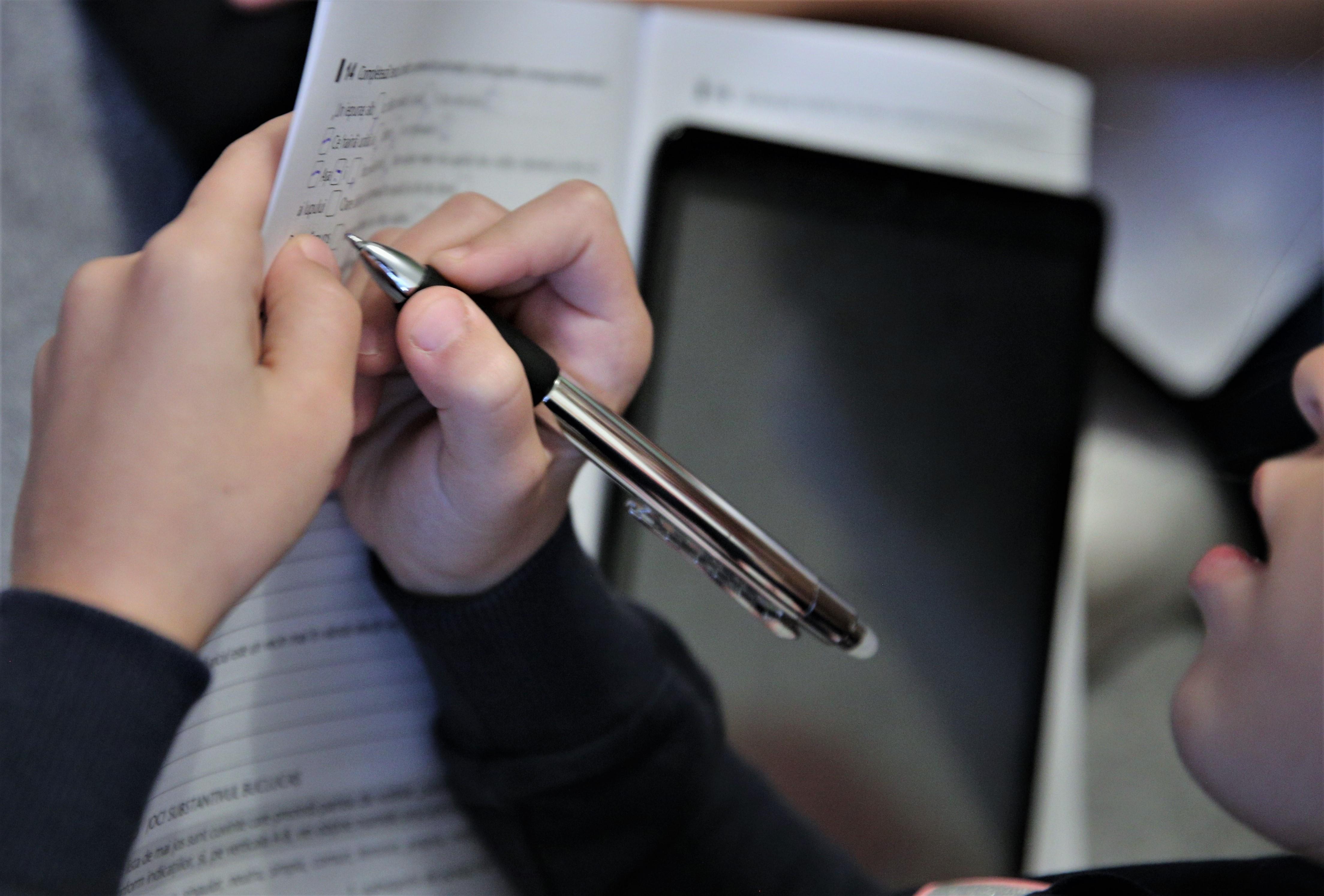 o fetită își face lecțiile cu o tabletă lângă caiet