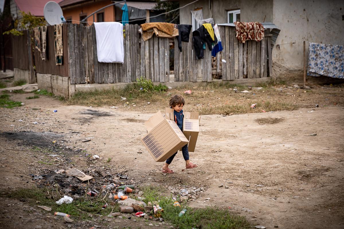 Un copil pe o uliță cu două cutii în mână