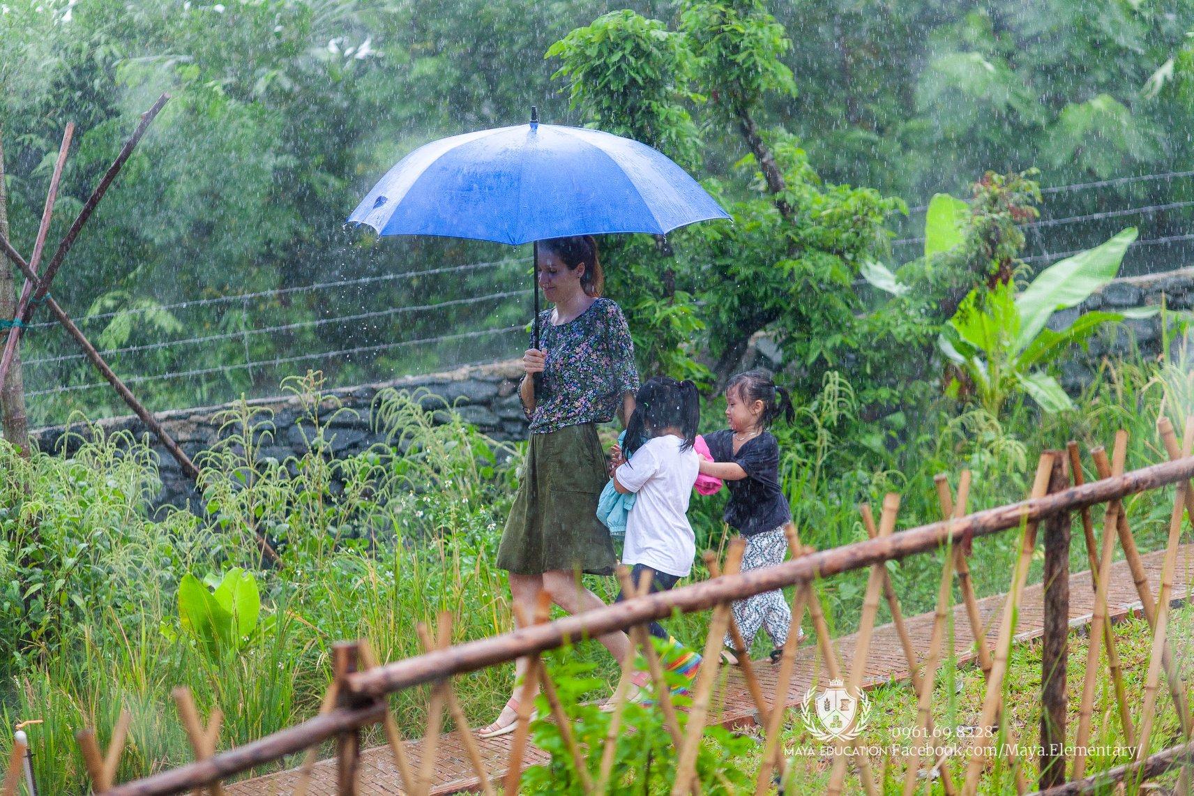 Simona și doi copii de grădiniță, mergând prin ploaie
