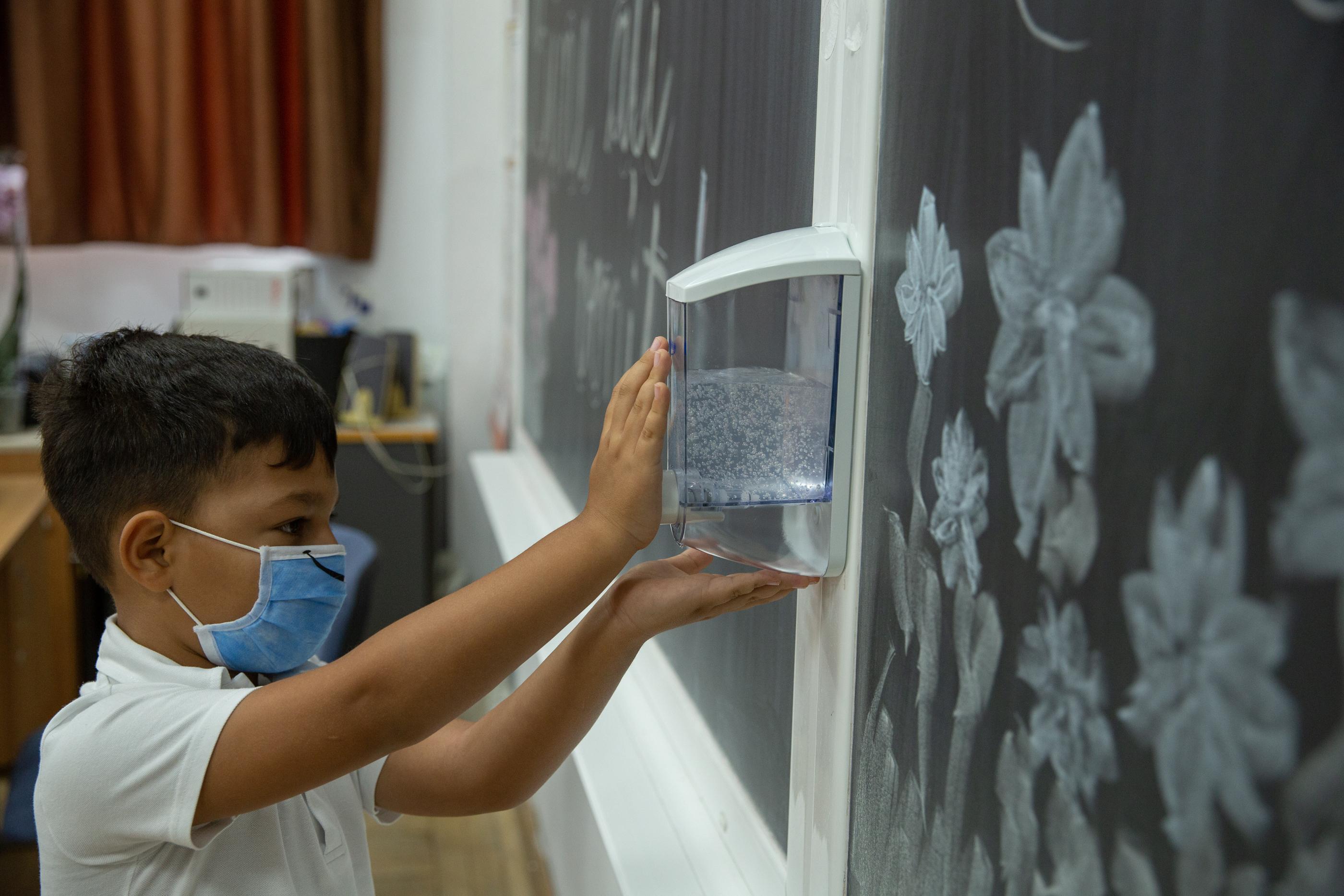 Un băiat își dezinfectează mâinile în clasă